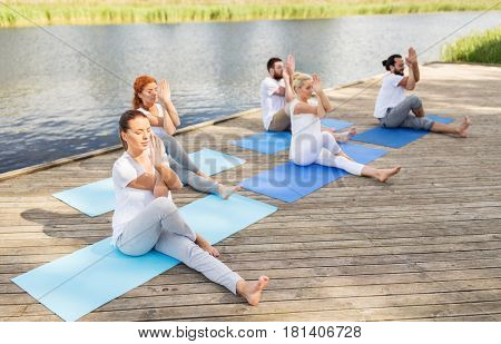 fitness, sport and healthy lifestyle concept - group of people making yoga exercise and meditating outdoors on river or lake berth