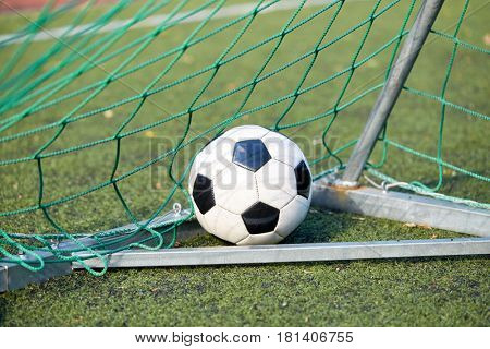 sport, soccer and game - ball at goal net on football field