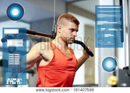 sport, fitness, bodybuilding and people concept - man exercising and flexing muscles on cable machine in gym over virtual charts