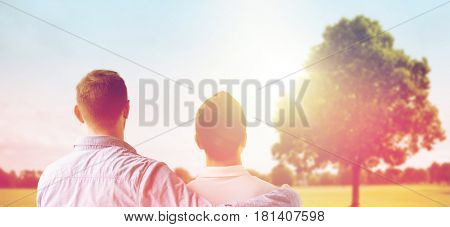 people, homosexuality, same-sex marriage and love concept - close up of happy male gay couple or friends hugging from back over oak tree at summer park background