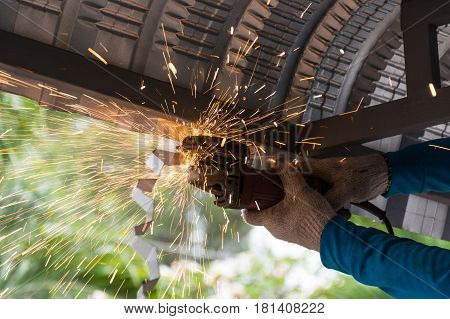 Worker grinding and cutting metalsheet of roof