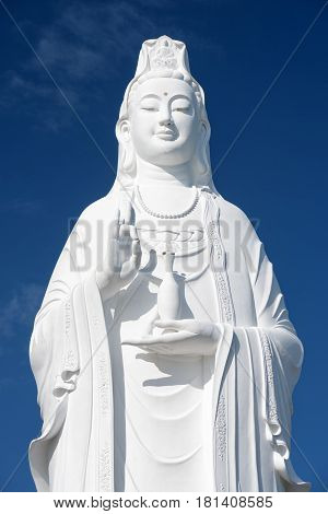 Majestic white Buddha statue on blue sky background. The Lady Buddha (the Bodhisattva of Mercy) at the Linh Ung Pagoda Danang (Da Nang) Vietnam.