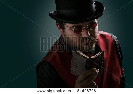Portrait of a man steampunk reading book in top hat and round glasses. Fantasy.