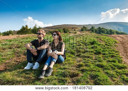 Young beautiful couple in sunglasses smiling, enjoying mountains lanscape, sitting on hill. Copy space.