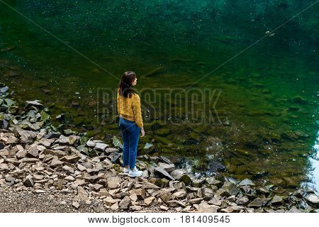 Young pretty brunette girl enjoying mountains lanscape, standing near lake. Copy space.