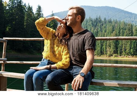 Young beautiful couple smiling, embracing, enjoying mountains lanscape. Copy space
