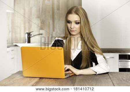 Portrait of a smiling young woman with laptop in the kitchen