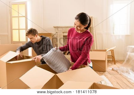 Serious Man And Smiling Woman Unpacking Things At New Home