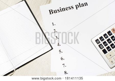 An inscription of the business plan execution points there is a notebook and a calculator next to it.