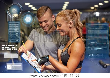 fitness, sport, exercising and people concept - smiling young woman with personal trainer and exercise plan on clipboard in gym over virtual charts