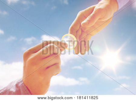people, homosexuality, safe sex, sexual education and charity concept - close up of happy male gay couple hands giving condom over sky and sun background