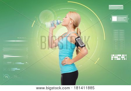 fitness, sport, people and technology concept - happy young woman running with earphones, smartphone and water bottle and listening to music over green background