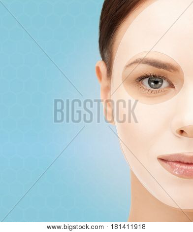 beauty, cosmetology, hydration, people and rejuvenation concept - close up of beautiful young woman half face with collagen facial mask over blue background