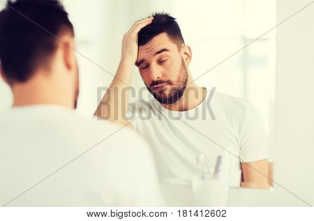 morning, awakening, hangover and people concept - sleepy young man in front of mirror at bathroom