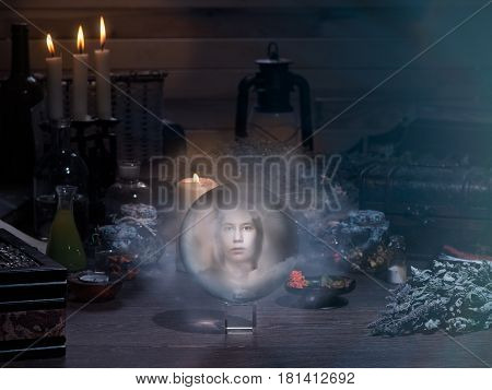 Mystical still-life. Women's ghostly face in the magic ball