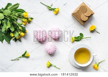 woman office desk with marsh-mallow and flowers in spring desing on white marble desk background top view