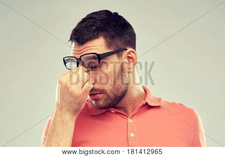 business, people, vision and overwork concept - tired man with eyeglasses touching nose bridge over gray background
