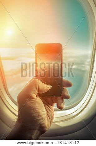 Hand with phone shooting sky with clouds under sun light in airplane. View from porthole at sunny day.