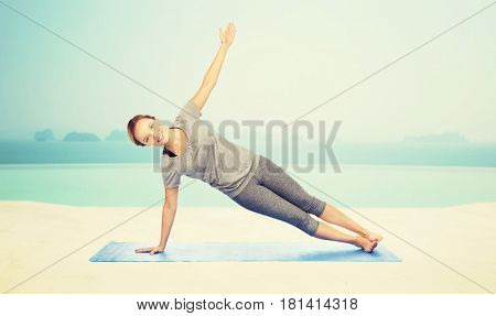 fitness, sport, people and healthy lifestyle concept - woman making yoga in side plank pose on mat over infinity edge pool at hotel resort background
