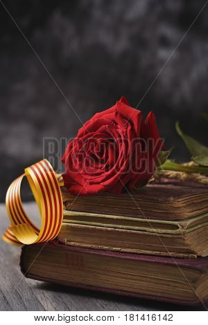 a red rose and a catalan flag on a pile of old books, on a rustic table, for Sant Jordi, the Catalan name for Saint Georges Day, when it is tradition to give red roses and books in Catalonia, Spain