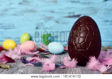 closeup of a chocolate egg on a rustic wooden table sprinkled with feathers of different colors and some different easter eggs, against a blue rustic background, with a blank space on the left