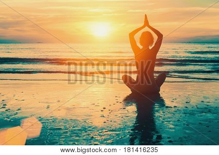 Meditation yoga silhouette of woman on the Sea beach at sunset.