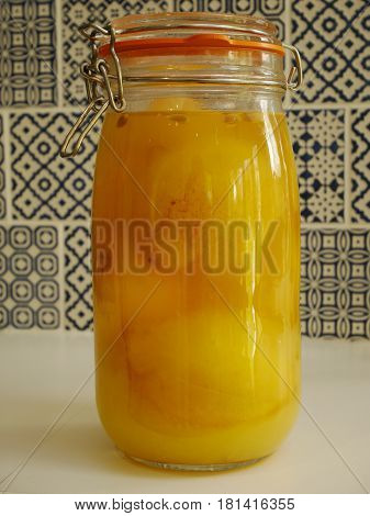 Tall glass storage jar containing pickled lemons
