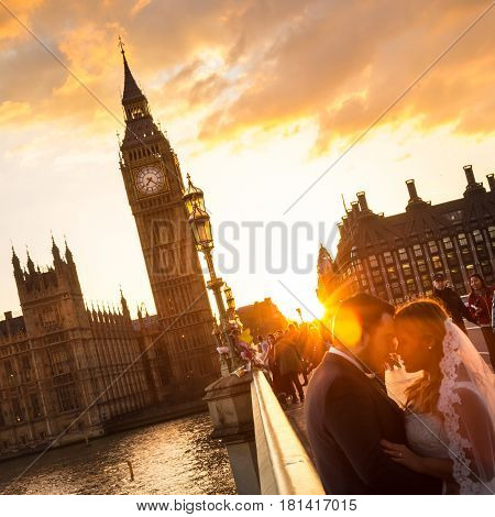 London, UK - April 2, 2015: People on Westminster Bridge in sunset on 2th of April, 2017 in London. Big ben and Palace of Westminster aka Houses of Parliament in background.
