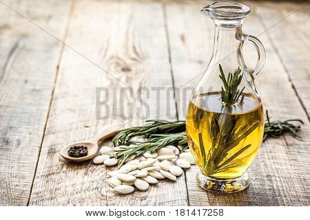 jar with natural oil with pepitas and rosemary on wooden table background mock up