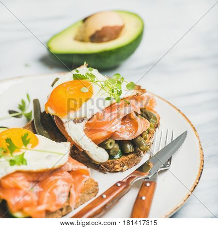 Healthy breakfast sandwiches. Salmon, avocado, fried egg, sauted green beans and fresh sprouts sandwiches in white plate over marble background, selective focus, square crop. Clean eating food concept