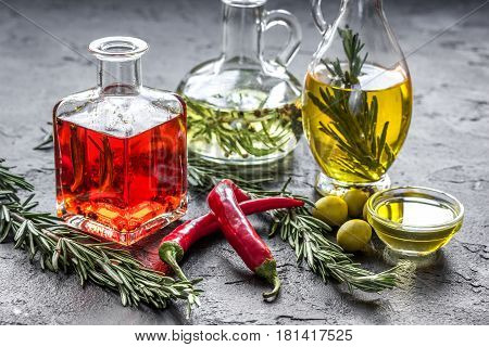 jar with natural oil with fresh chili, olives and rosemary on stone table background