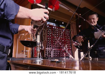 Man pouring red wine into glass decanter