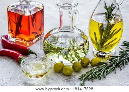 organic olive, pumpkin seed and chili oil with fresh ingredients on stone kitchen table background