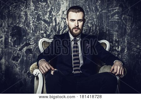 Respectable handsome man sitting in classical vintage armchair. Men's beauty, fashion. Luxurious lifestyle.
