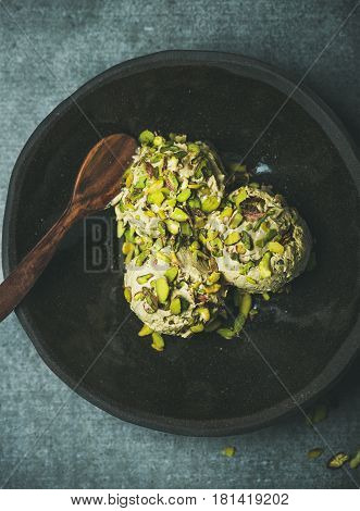 Homemade pistachio ice cream scoops with crashed pistachio nuts in dark plate over grey concrete background, top view, vertical composition
