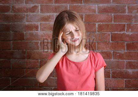 Cute girl suffering from headache near brick wall