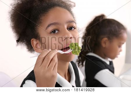 Cute African-American girl in dinning room at school