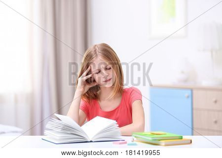 Cute girl suffering from headache while doing lessons at home