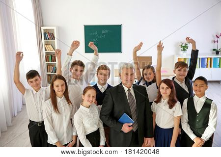 Happy pupils and senior teacher standing in classroom