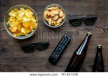 watching movies set with chips, beer and remote control on wooden background top view