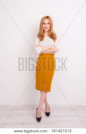 Full-length Vertical Portrait Of Beautiful Smiling Businesslady With Crossed Hands Isolated On White