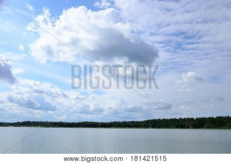 Clouds on a blue sky over a lake in summer
