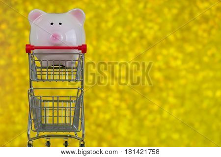 Closeup of pink piggy bank pig standing on mini shopping push cart on blurred yellow Bokeh background copyspace