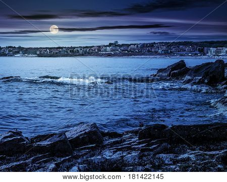 SOZOPOL BULGARIA - SEPTEMBER 11 2013: rocky shore and sandy city beach in mellow season. Beautiful and warm weather on the coast of Black sea at night in full moon light