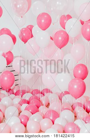 The room filled with the pink colored balloons. Vertical indoors shot.