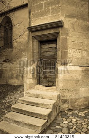 Entrance door of the Lutheran Cathedral in the old medieval city of Sibiu, Romania. Aged photo look.
