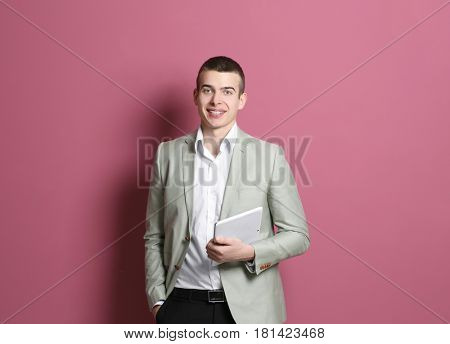 Young handsome man with tablet on color background