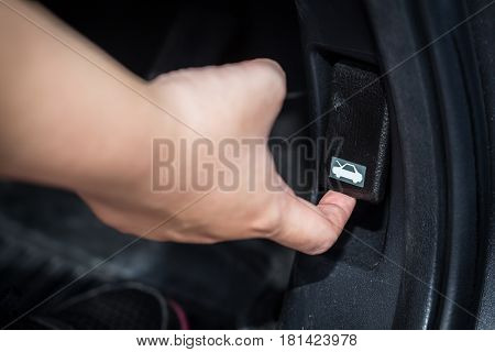 women hand open car hood unlock switch.
