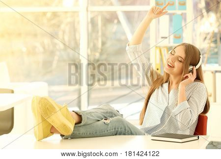 Beautiful young woman listening to music indoors