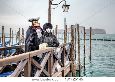 Elegant masked couple with carnaval costumes wearing fur, Venice, Italy.